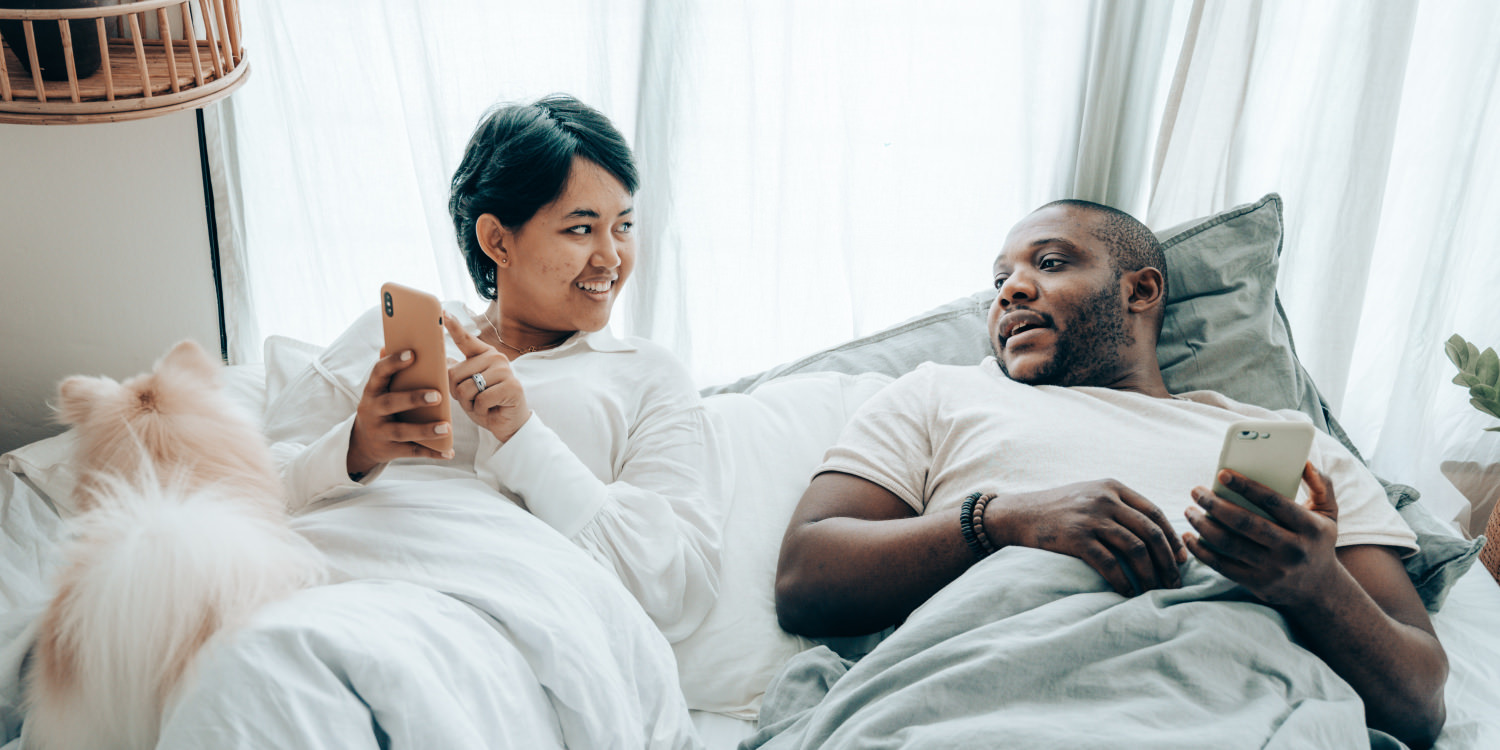 A South Asian woman and her husband, who is black, are waking up from sleep and talking. A small fluffy light brown dog is in the left side of the picture.